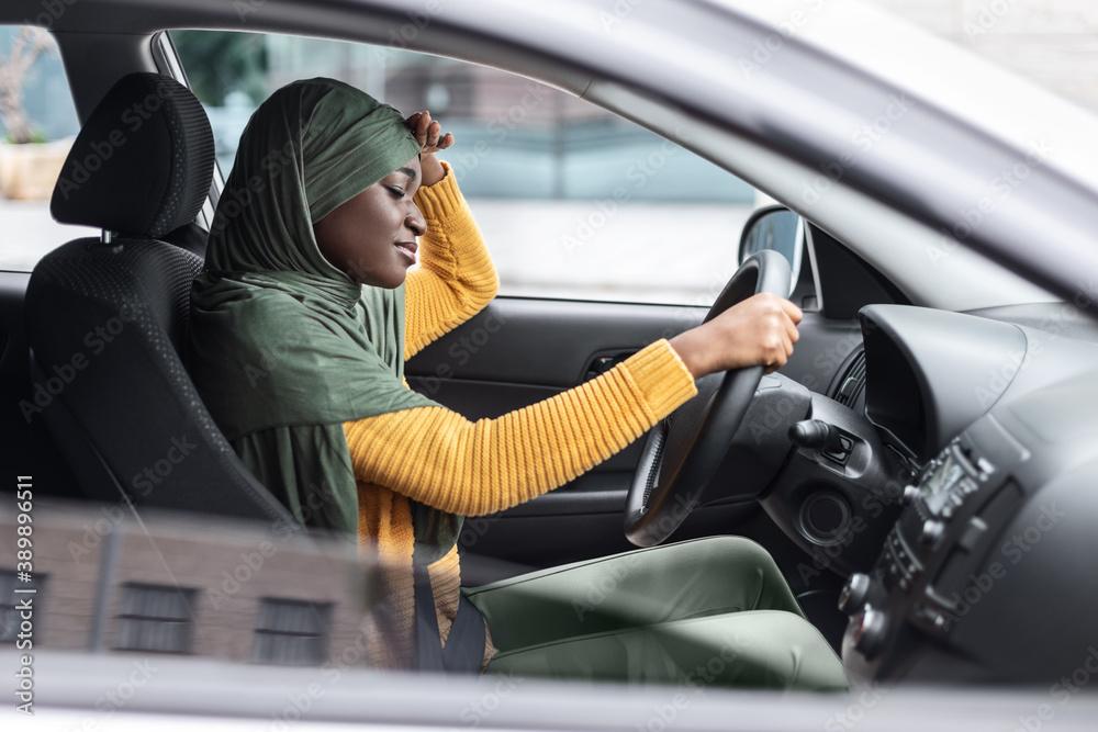 Fototapeta Tired African Muslim Lady Driving Car, Having Headache And Feeling Sleepy