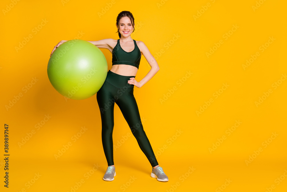 Fototapeta Full length body size view of nice attractive healthy cheerful girl carrying pilates fitness ball posing isolated over bright yellow color background.