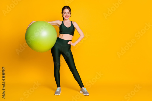 Fototapeta premium Full length body size view of nice attractive healthy cheerful girl carrying pilates fitness ball posing isolated over bright yellow color background.