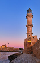 Egyptian Lighthouse Of Old Venetian Harbour Of Chania, Crete, Greece At Sunrise. Soft Sky From Blue To Pink, Vertical Shot Against Firka Castle Walls.