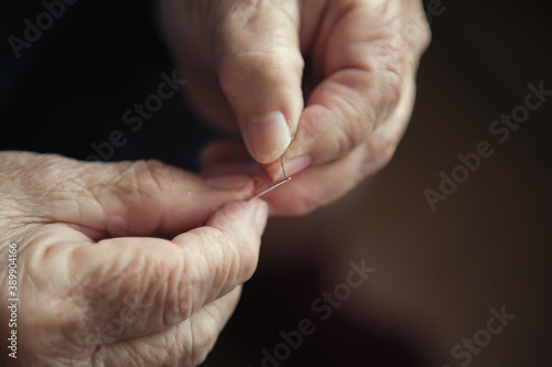 Fotografering Old woman's hands are threaded in the needle.
