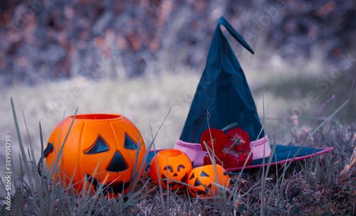 Cuadros en Lienzo paisaje con calabazas de halloween y sombrero de bruja sobre fondo morado
