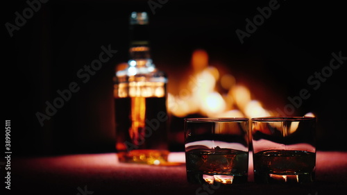 Papel de parede A bottle of strong alcohol stands on the table by the fireplace, in the foregrou