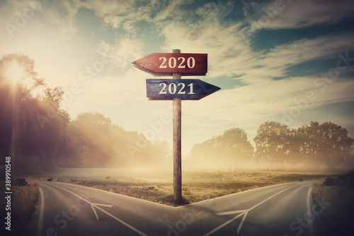 Fotografie, Obraz Surreal scene with a split road and signpost arrows showing two different courses, left and right, past and future, old 2020 and the new 2021 year direction to choose