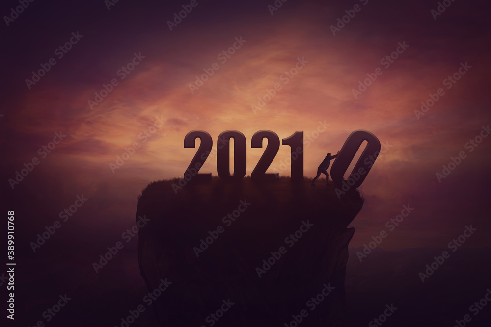 Fototapeta Silhouette of a determined man on the top of a cliff over sunset, announcing the new 2021 year coming, and throws out in the abyss the old 2020. Surreal seasonal scene, change concept and time control