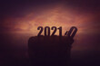 Silhouette of a determined man on the top of a cliff over sunset, announcing the new 2021 year coming, and throws out in the abyss the old 2020. Surreal seasonal scene, change concept and time control