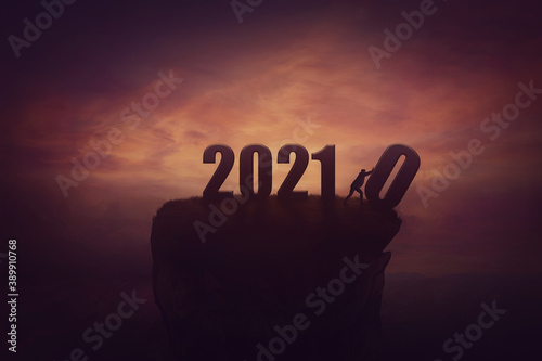 Fototapeta Silhouette of a determined man on the top of a cliff over sunset, announcing the new 2021 year coming, and throws out in the abyss the old 2020. Surreal seasonal scene, change concept and time control obraz