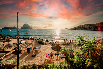 Picturesque view of Cala d'Hort tropical Beach, people hangout in beautiful beach with Es Vedra rock view during magnificent vibrant sunset glowing sun. Balearic Islands. Ibiza, Spain