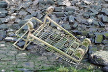 Discarded Metal Shopping Trolley On Rocky  Riverbed