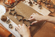 Hands Cutting Gingerbread Dough With Man, Star And Tree Metal Cutters On Rustic Table
