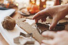 Hands Cutting Gingerbread Dough With Christmas Tree Metal Cutter On Table With Festive Lights