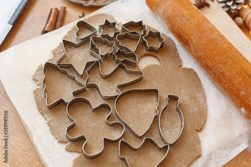 Raw gingerbread dough with festive metal cutters, wooden rolling pin, decorations on rustic table