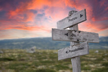 Focus On Possibilities Text Engraved In Wooden Signpost Outdoors In Nature During Sunset And Pink Skies.