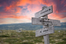 Unlimited Boundless Infinite Text Engraved In Wooden Signpost Outdoors In Nature During Sunset And Pink Skies.