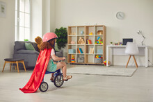 Back View Of A Little Curly Girl In A Red Cloak And Helmet Rides A Tricycle At Home In The Room.