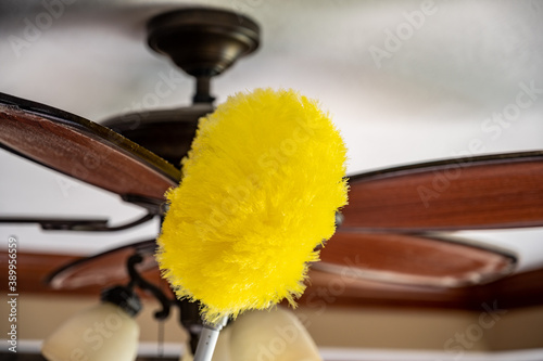 Photo Using a wand feather duster to remove and clean dust from a ceiling fan