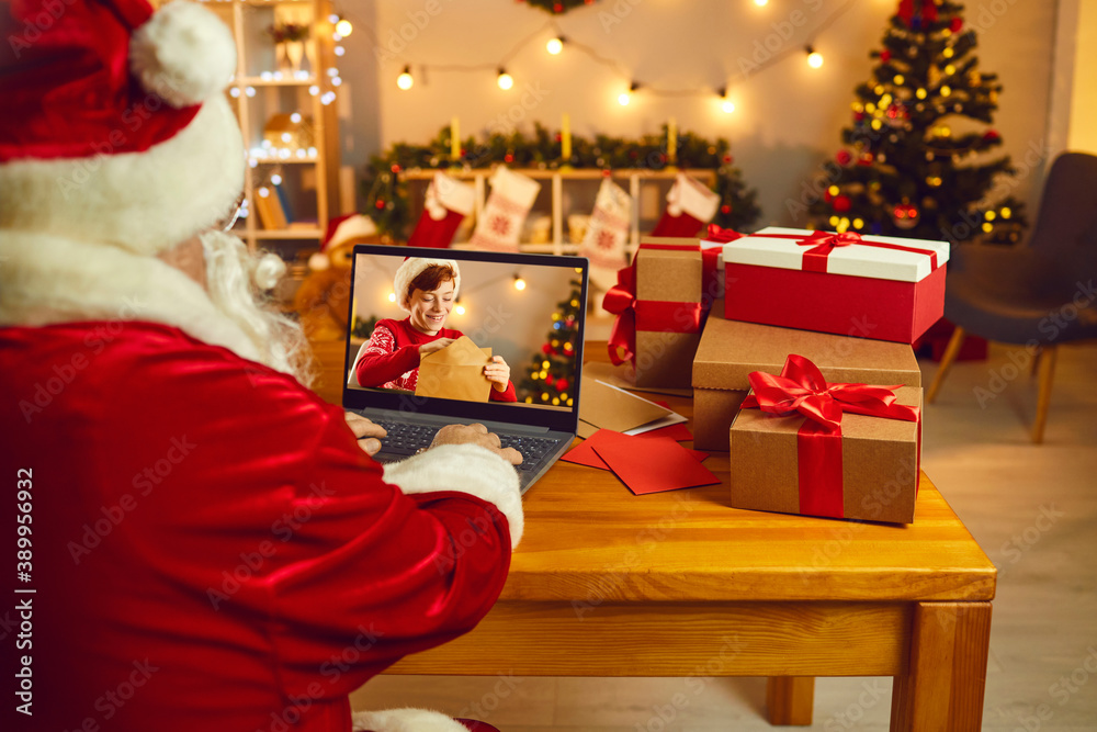 Fototapeta Santa looking at laptop screen spying on little boy who's writing and sending Christmas letter