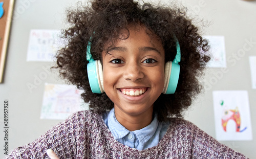 Happy african american mixed race kid child girl wearing headphones looking at camera or web cam remote distance learning on video conference call, virtual class, headshot close up face portrait Canvas