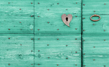 Close-up Of An Old Wooden Turquoise-colored Exterior Door With An Iron Handle And A Lock