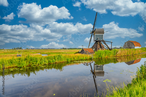 Dutch polder landscape with watermill the Blauwe Wip along the drain canal  for Fototapeta