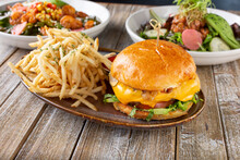 A View Of Several Gastropub Entree Fare, Featuring A Cheeseburger And French Fries Plate.