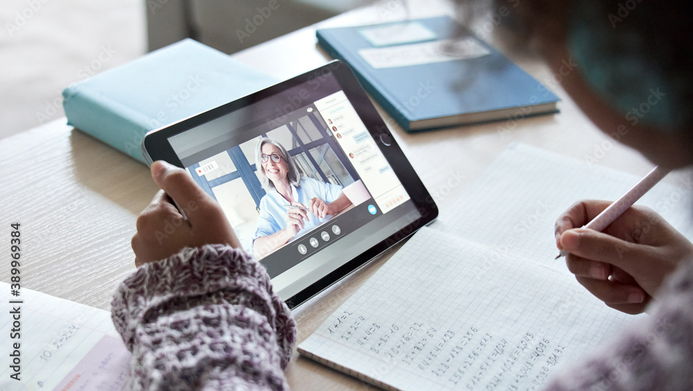 Fototapeta African american school kid child girl holding digital tablet talking to remote teacher tutor on social distance video conference call study online virtual class learning at home, over shoulder view.