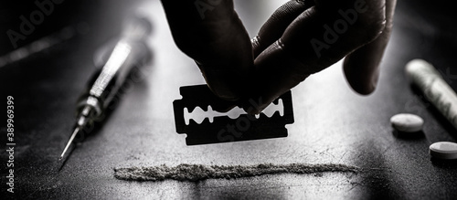 Foto hand separating with a blade a portion of cocaine, white powder to be inhaled, c