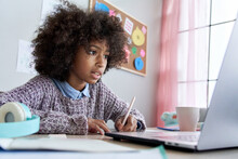 Cute Smart African American School Pupil Kid Girl Virtual Distance Learning Online Watching Remote Digital Class Lesson Looking At Laptop Computer Tech Studying At Home Writing Notes Sitting At Desk.