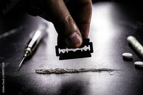hand separating with a blade a portion of cocaine, white powder to be inhaled, c Fototapete