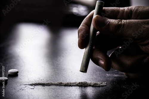 Fototapeta hand holding money straw to inhale a portion of cocaine, white powder to be inhaled, concept of addiction and drug addiction, dealer and sale of drugs obraz