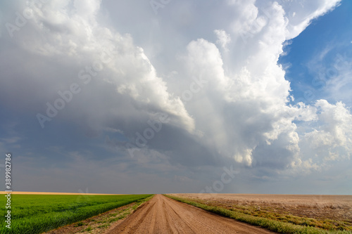 Fototapety, obrazy: Scenic summer landscape with a dirt road, storm clouds, and farm field in Kansas