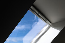 Interior View And Close-up Detail At Closed White Tilt Window Skylights At Attic And Background Of Sunny Blue Sky.