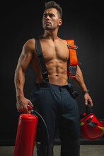 Portrait Of A Muscular, Handsome Firefighter On A Dark Background, Holding A Fire Helmet, Looking To The Side