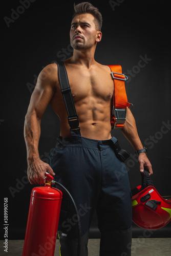 Canvas Print portrait of a muscular, handsome firefighter on a dark background, holding a fir
