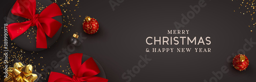 Fototapeta Christmas banner. Background Xmas design of realistic black gift box red bow, 3d render bauble ball and glitter gold confetti. Horizontal christmas poster, greeting card, headers for website obraz