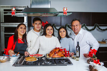 Latin American Family Cooking Turkey For Mexican Christmas Eve Dinner On The Kitchen