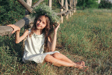 Cute Little Girl Wearing Wreath Made Of Beautiful Flowers Near Wooden Fence Outdoors On Sunny Day