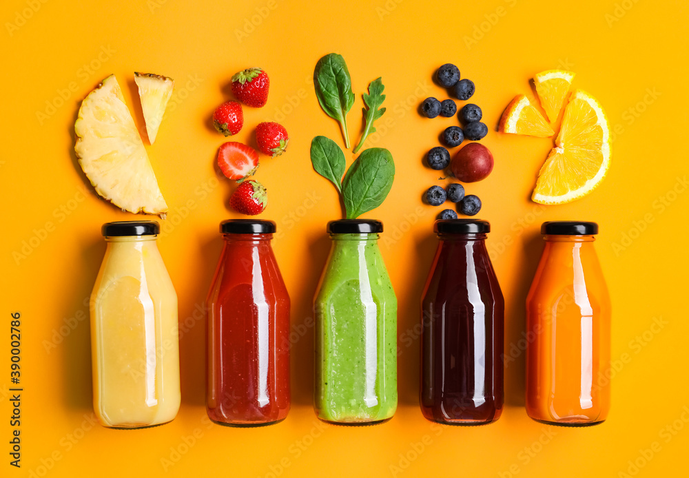 Fototapeta Flat lay composition with bottles of delicious juices and fresh ingredients on orange background