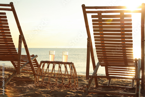 Photo Wooden deck chairs and wicker table with cocktails on sandy beach