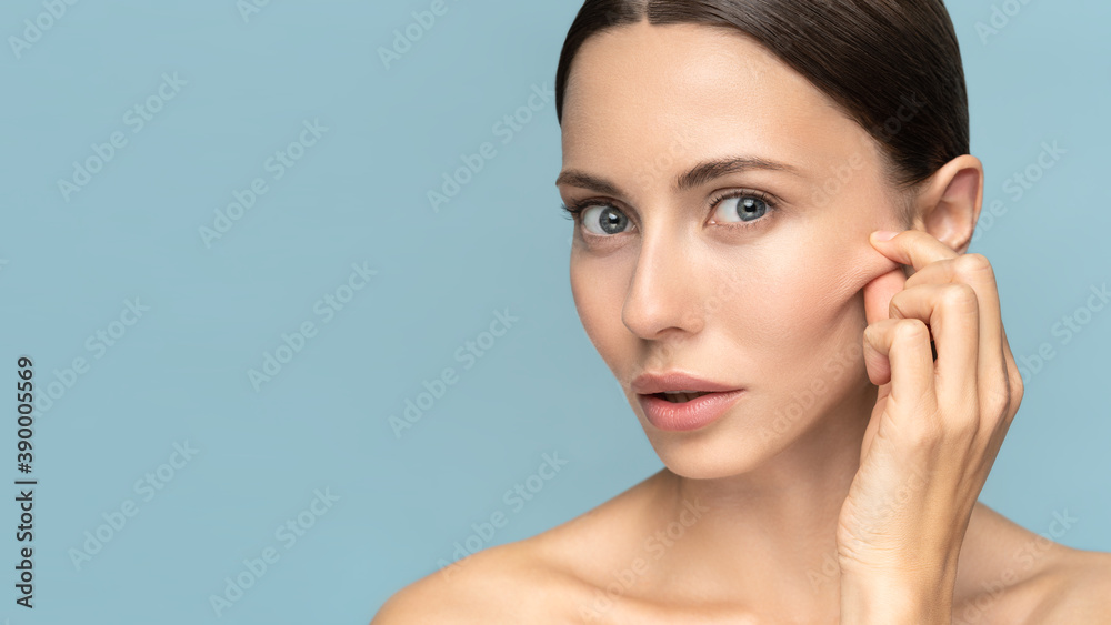 Fototapeta Woman without makeup touching cheeks after glycolic acid peel, has signs of aging skin on her face, looking at camera, isolated on studio blue background. Beauty skincare, cosmetology facial treatment