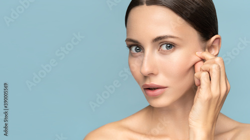 Obraz Woman without makeup touching cheeks after glycolic acid peel, has signs of aging skin on her face, looking at camera, isolated on studio blue background. Beauty skincare, cosmetology facial treatment - fototapety do salonu
