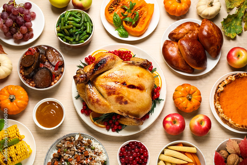 Fototapeta Traditional Thanksgiving day feast with delicious cooked turkey and other seasonal dishes served on wooden table, flat lay obraz