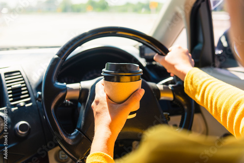 Asian woman drinking hot coffee takeaway cup inside a car and while driving the Billede på lærred