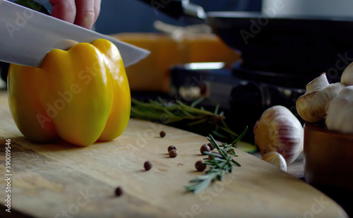Tela Cutting vegetables, yellow sweet pepper on a wooden board with a kitchen knife