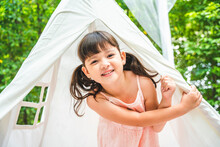 Cute Little Girl Enjoy Staying In White Camping Tent In Garden.
