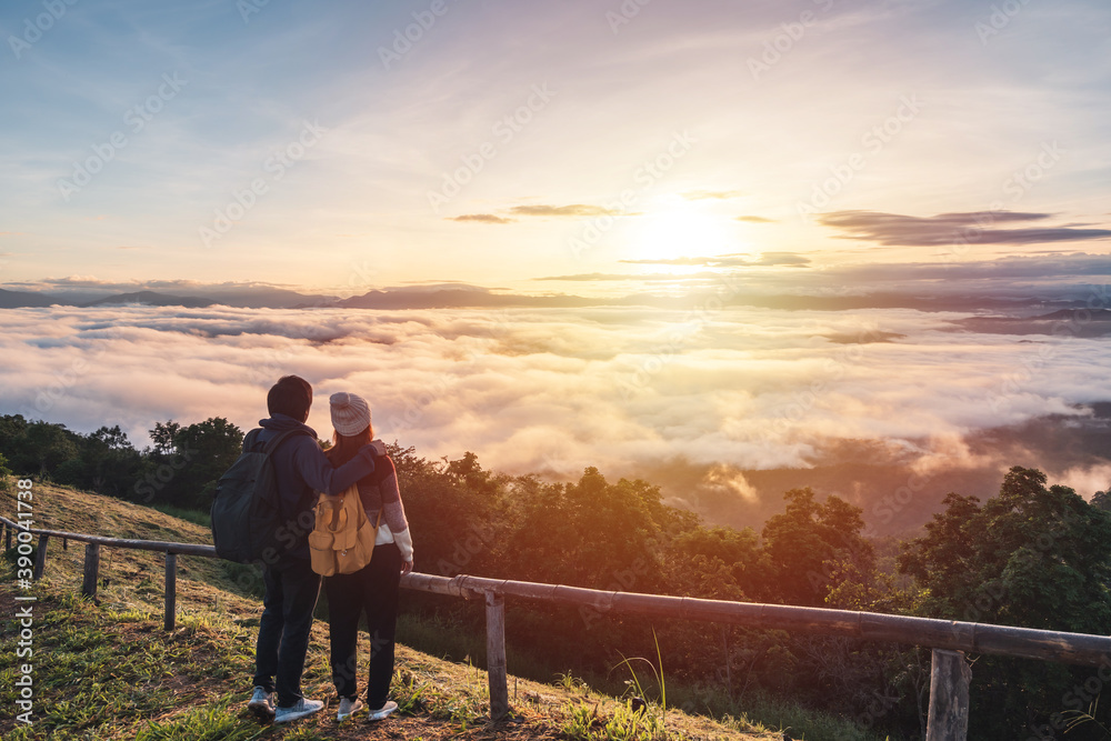 Fototapeta Young couple travelers looking at the sunrise and the sea of mist on the mountain in the morning, Travel lifestyle concept