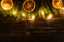 Christmas Background With Fur-tree Branches, Dried Oranges And Led Garland On Wooden Background.