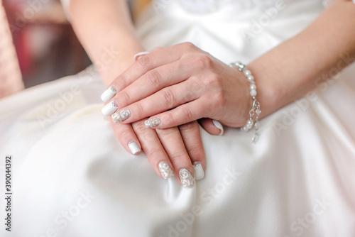 Fotografia Hands of the bride on a white wedding dress