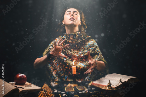 Obraz Astrology, magic and divination. The sorceress creates the magic of divination over a candle. Black background. There are magic items on the table - fototapety do salonu