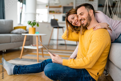 Couple in love hugging and using tablet together.
